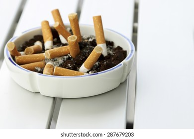 Cigarette butts in ashtray on white table.