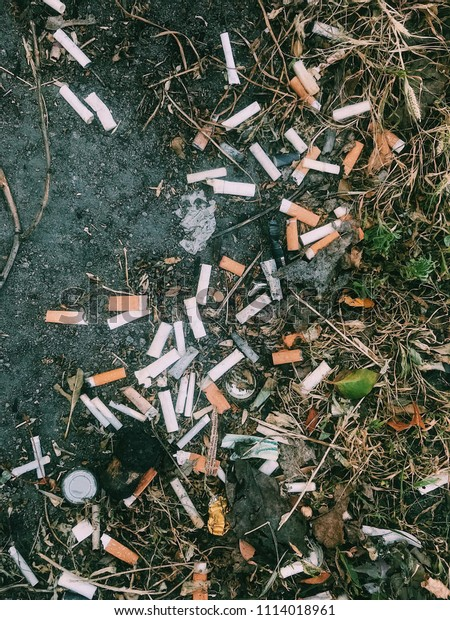 Cigarette butts and bottle caps lying on the ground in the city. Top view.