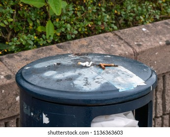 Cigarette butts stubbed out on a waste bin