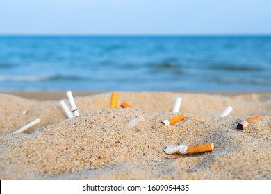 Cigarette butts in yellow sand on sea beach on coast against background of blue sky and sea. Problem of humanity.  Cigarette smoking, a bad habit. Nicotine addiction. Garbage