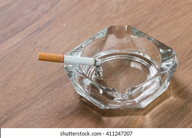 cigarette and a glass ashtray on an old wooden table