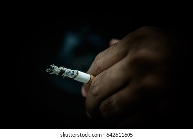 Cigarette in hand of asian handsome man,low key style