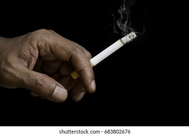 A cigarette in hand isolate on black background.