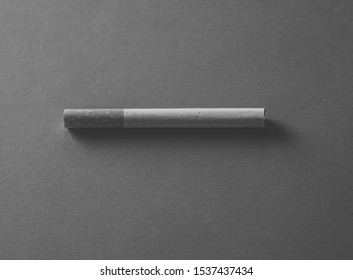 Cigarette isolated. Conceptual image in black and white with copy space for text. Advertising style of stop smoking, smoking causes disease, dangers of tobacco, nicotine addiction and medical warning.