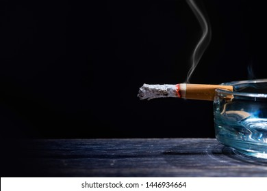 Cigarette on transparent ashtray on wooden table with black background