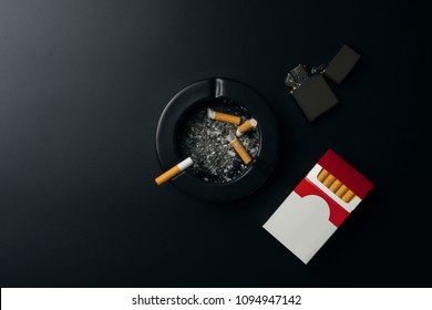 cigarette pack, chrome lighter and black ceramic ashtray full of ashes with the cigarette butt, on the black table