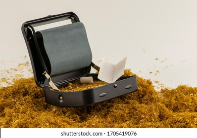 Cigarette rolling machine with heap of tobacco. Handmade cigarette roller.