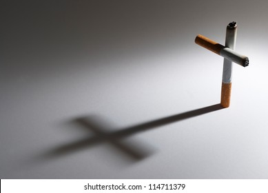 A cigarette with it shadow making a cross