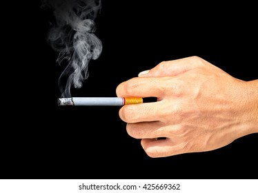 Cigarette and smoke in the hand on black background
