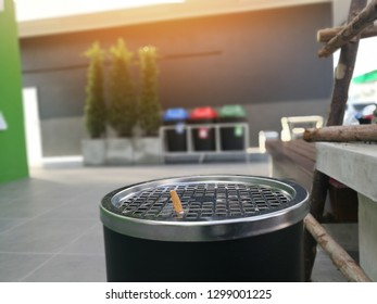 Cigarette stub in ashtray at smoking area. Closeup view of big ashtray with dropped cigarettes