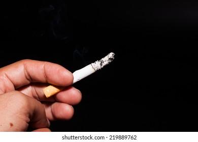 cigarette stub in hand