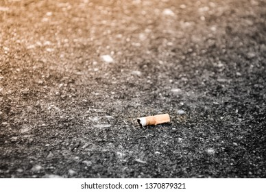 Cigarette stub isolated on the cement floor background with copy space.Smoked cigarette stub.