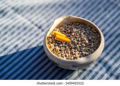 cigarette stub in sand bucket ashtray
