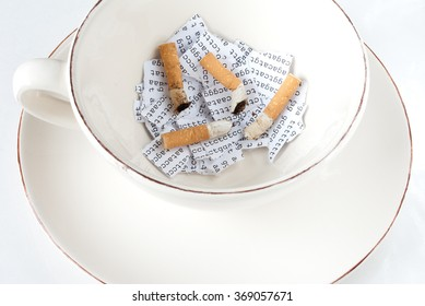 Cigarette stubs on a torn DNA sequence in a coffee cup