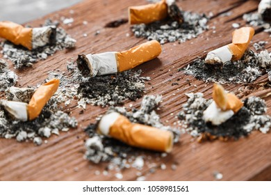 Cigarette stubs on a wooden background close up