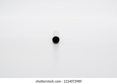 A cigarette with a white filter laying vertical isolated on a white background