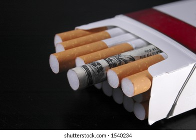 A cigarette wrapped in a dollar bill in a pack of cigarettes.