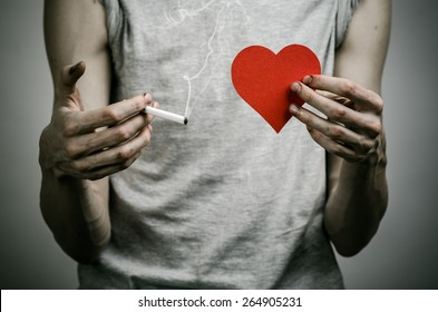 Cigarettes, addiction and public health topic: smoker holds the cigarette in his hand and a red heart on a dark background in the studio