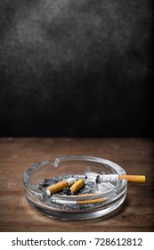 Cigarettes with ashtray on wooden background