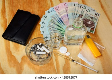 Cigarettes, drugs, tablets, boosters, syringe, vodka and money polish are wooden table