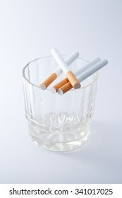 Cigarettes in glass on white background