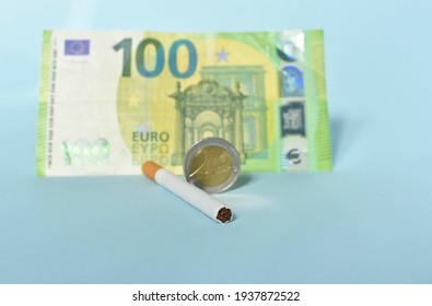 Cigarettes and money on blue background. Euro banknotes and coins, cost of smoking, cigarette price concept. Selective focus