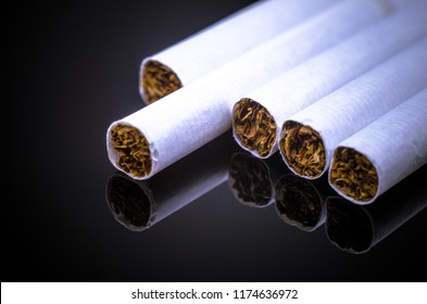 Cigarettes on the black glass with reflection. Tobacco side. Macro texture. Darkening effect.