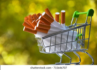 cigarettes in a shopping cart.Many cigarettes on an evil background