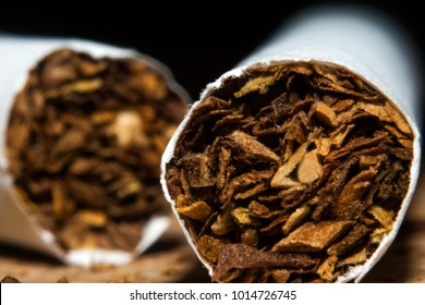 cigarettes and tobacco on a brown wooden background, closeup