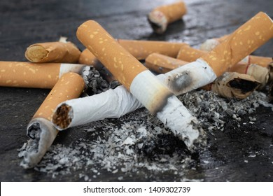 Cigarettes were burnt and smoking.World No Tobacco Day falls on May 31 of every year.Smoke cigarettes were smashed,Close-up shots On black wood floor.shallow focus effect.