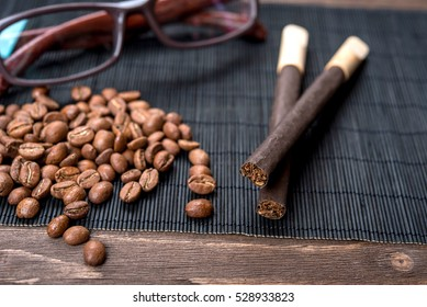 Cigarillos, cigars, coffee beans and glasses on a bamboo napkin