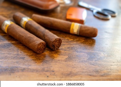 Cigars and accessories on a wooden office desk, closeup view. Cuban quality cigar tobacco smoking luxury lifestyle.