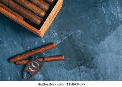 Cigars, Guillotine cuts off the cigar tip, black background , space for text, copy space. Wooden box, cigars.