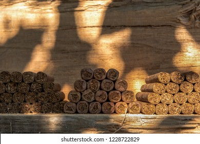 Cigars lie stacked on a wooden table in several blocks. Concept: cigars or health or livestyle