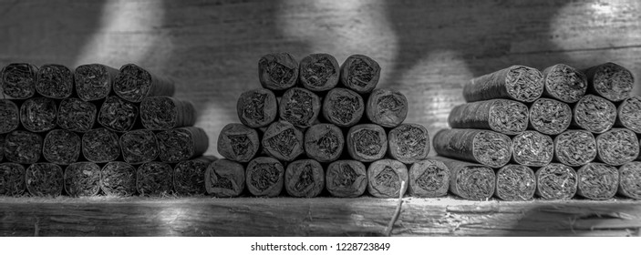 Cigars lie stacked on a wooden table in several blocks. View in black and white. Concept: cigars or health or livestyle
