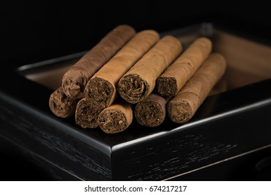 Cigars on top of a black humidor. Rich smelling and textures of tobacco leaves