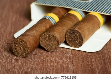 Cigars in the package on mahogany boards.