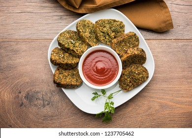 Cilantro cake or Kothimbir Vadi is a popular maharashtrian cuisine made with cilantro leaves. served with tomato ketchup. selective focus