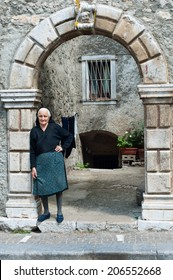 Cilento, Italy - July 29, 2011: Old italian woman stays in Cilento arch of her house. Photo taken on 29th of July, 2011 in Cilento and Vallo di Diano National Park.