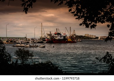Cinarcik, Turkey - October 9, 2016: Fishermen shelter and seashore establishment with fishing boats over calm sea by the side of Marmara region during a calm evening of winter