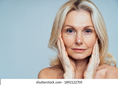 Cincematic image of a beautiful senior woman posing on a beauty photo session. Middle aged woman in lingerie on a grey background. Concept about body positivity, self esteem, and body acceptance