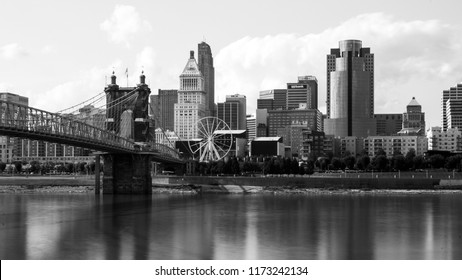Cincinnati, OH—August 30, 2018; black and white image of the Cincinnati skyline and riverfront with steel roebling suspension bridge over water and reflections on water.
