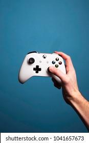 CINCINNATI, OH, USA - CIRCA 2018: Hand holding a white Xbox 360 wireless video game controller.