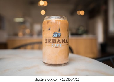 Cincinnati, OH / USA - March 28 2019: Close up of an iced dirty chai in a glass pop  can-sized glass at the East Walnut Hill's Urbana Cafe coffee shop location on Woodburn Ave. Light airy coffee shop.