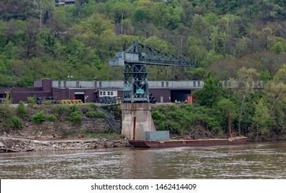 Cincinnati, Ohio / USA - April 25, 2019: View of crane and facilities at the Cincinnati Barge & Rail Terminal, LLC form the Ohio river.