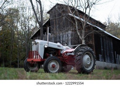CINCINNATI, OHIO / USA - October 30 2018: Old fashioned rustic American-made Ford N-Series 4 cylinder farm tractor inline engine with a rustic barn in the background in wooded Autumn setting.