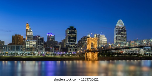 CINCINNATI, OHIO/USA - JULY 6, 2018: Night cityscape of the Cincinnati skyline, the Ohio River and the John A. Roebling Suspension Bridge