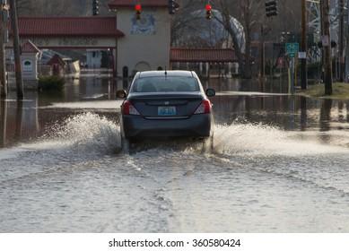 CINCINNATI, OHIO/USA, MARCH 16, 2015: A man drives through floodwaters at the entrance of the  Coney Island amusement park in Cincinnati, Ohio.