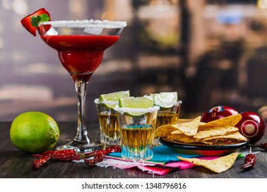 Cinco de Mayo celebration background. 5th May Mexican party. Strawberry mojito, corn nachos and tequila shots with lime on wooden table