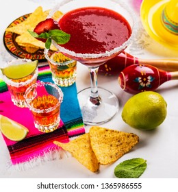 Cinco de Mayo celebration background. 5th May Mexican party. Strawberry mojito, corn nachos and tequila shots with lime on white table